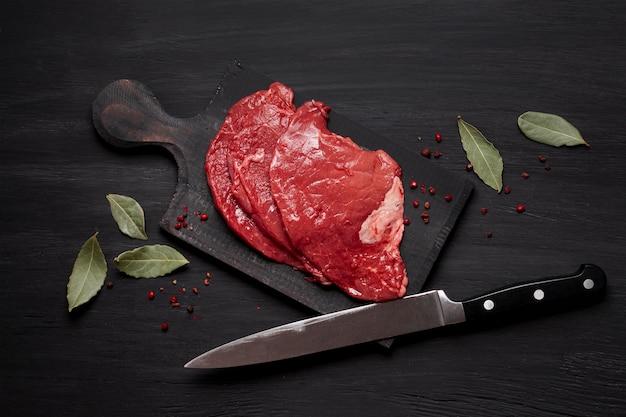 Carne cruda fresca sobre tabla de madera con cuchillo