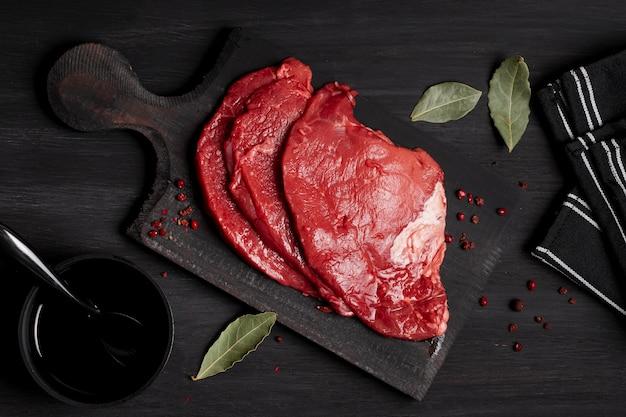 Carne cruda fresca sobre tabla de madera con salsa de soja