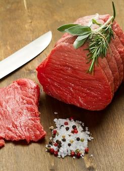 Carne cruda en mesa de madera con romero, salvia y sal.