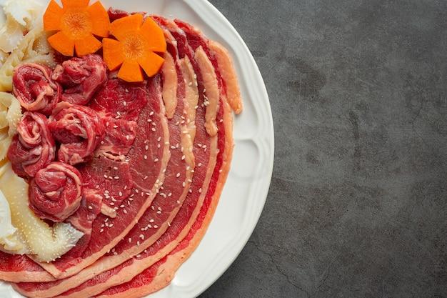 Carne cruda en un plato blanco para el menú de olla caliente shabu