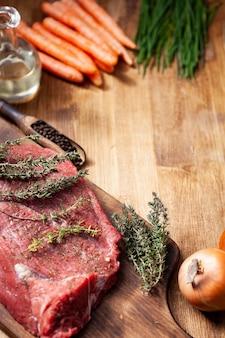 Carne cruda servida con verduras y hierbas decoradas sobre tabla de madera rústica.
