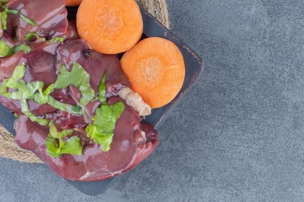 Carne cruda y verduras frescas en tablero oscuro.