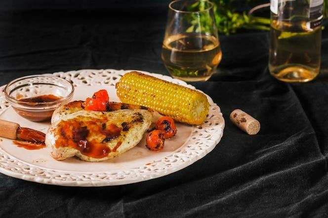 Carne de cerdo servida con tomates cherry y mazorca de maíz en un plato