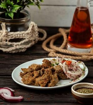 Carne con especias y cebolla con zumaque en una mesa de madera