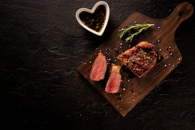 Carne fresca a la brasa. filete de ternera a la parrilla medio raro sobre plancha de madera. vista superior.