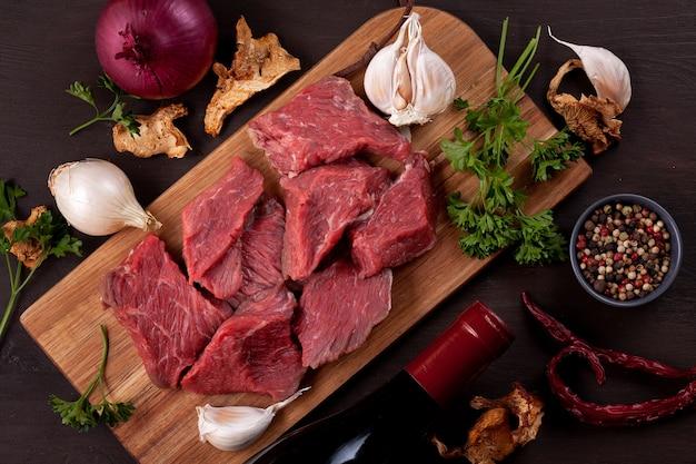 Carne fresca cruda, botella de vino y verduras orgánicas estacionales de otoño sobre tabla de madera lista para cocinar