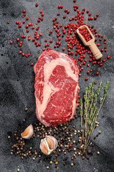 Carne fresca cruda ribeye steak con condimento. filete de res a la costilla. fondo negro. vista superior