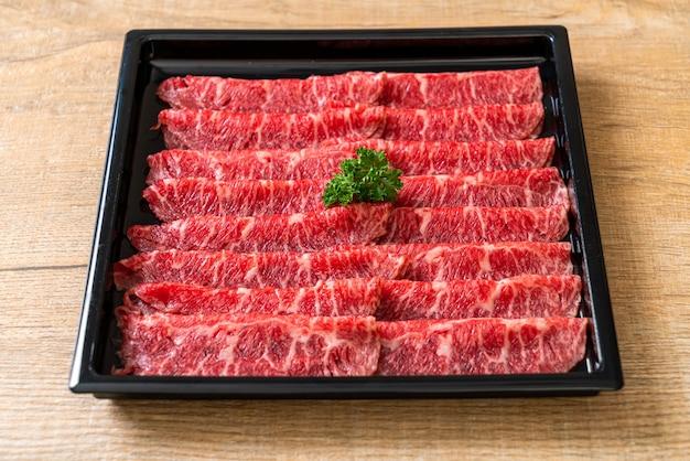 Carne fresca cruda en rodajas con textura marmolada servida para sukiyaki y shabu o yakiniku