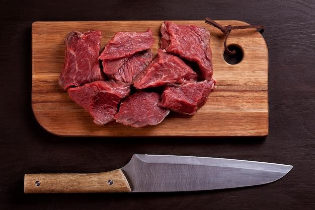 Carne fresca cruda en tablero de madera listo para cocinar