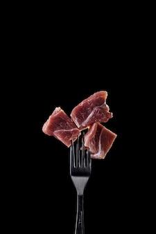 Carne fresca y cruda en un tenedor.
