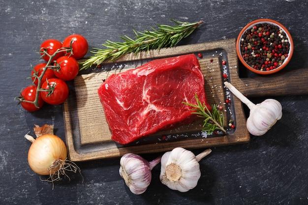 Carne fresca con ingredientes para cocinar sobre tabla de madera, vista superior