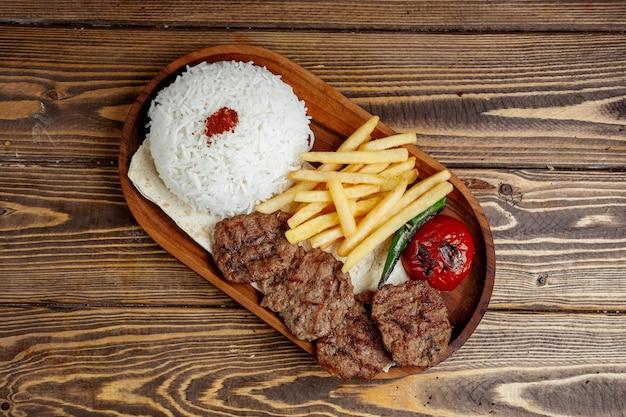 Carne frita con arroz y papas fritas