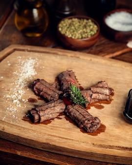 Carne frita enrollada en un rollo sobre una tabla de madera