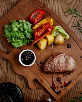 Carne frita con papas y verduras sobre tabla de madera