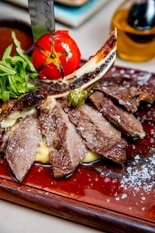 Carne frita servida con rúcula y tomate a la parrilla
