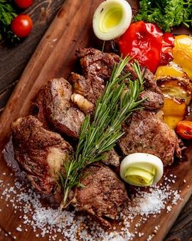 Carne frita servida con vegetales a la parrilla cebolla y ramita de romero