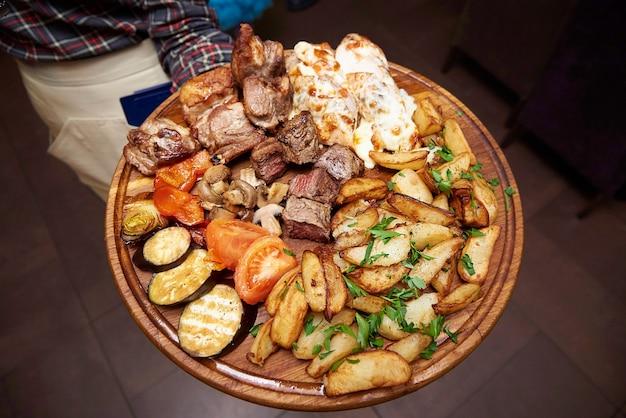 Carne frita y verduras cocidas en un tablero de madera en las manos de un camarero en un restaurante.