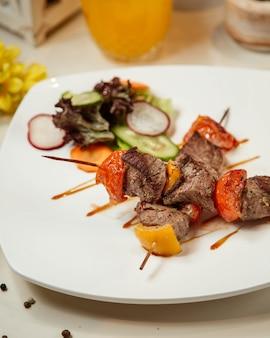 Carne frita y verduras en palo