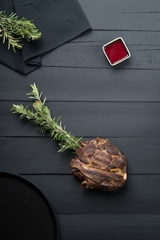 Carne frita con verduras, salsa y salsa sobre un fondo de madera negra