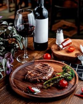 Carne frita con verduras y vino tinto.