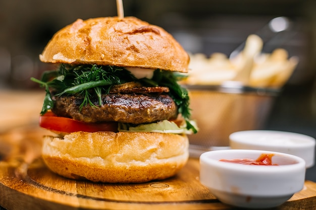 Carne hamburguesa tomate pepino verduras lechuga ketchup mayonesa vista lateral