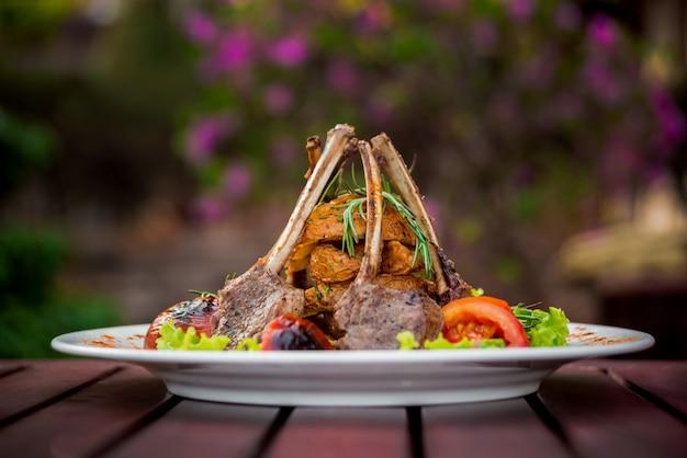 Carne en el hueso con verduras en un plato blanco. restaurante.