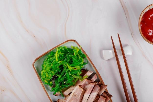 Carne japonesa de cerdo a la parrilla con algas y salsa