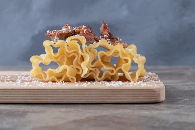 Carne en láminas de lasaña en el tablero, en la superficie de mármol.