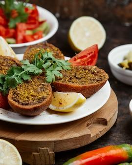 Carne molida en pan frito con rodajas de limón y tomate