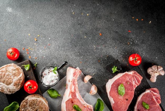 Carne orgánica cruda. selección de varios tipos de carne roja: chuleta de cerdo con hueso, filetes de cerdo y chuletas de pollo en rejilla de grasa de cerdo. con ingredientes para cocinar, vista de mesa de piedra gris