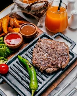 Carne y papas fritas caseras y naranja fresca