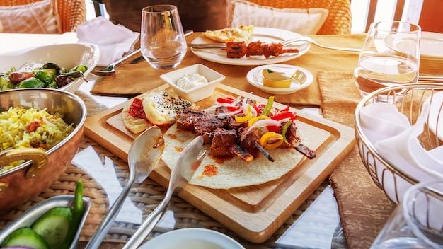 La carne de la parrilla de la barbacoa sirvió con las verduras tortilla y la salsa en tabla de cortar de madera. se sirve el almuerzo. foto de la luz del sol en tonos.