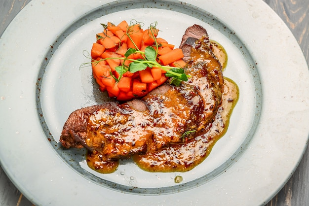 Carne a la parrilla con salsa y verduras guisadas en una mesa de madera