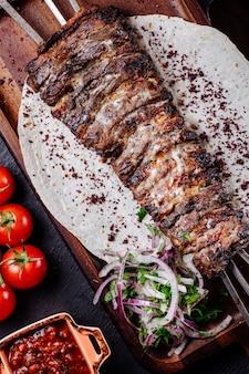 Carne a la parrilla sobre pan lavash con ensalada de cebolla y hierbas.