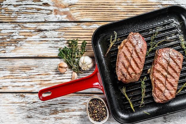 Carne a la parrilla top blade filetes en una sartén en gris. vista superior. copia espacio