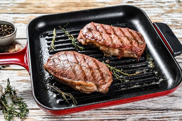 Carne a la parrilla top blade filetes en una sartén en gris. vista superior