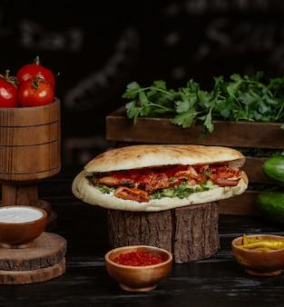 Carne a la parrilla y verduras rellenas dentro de un bollo de pan servido con hierbas y sumakh.
