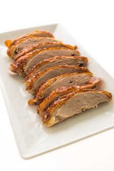 Carne de pato a la parrilla en plato blanco