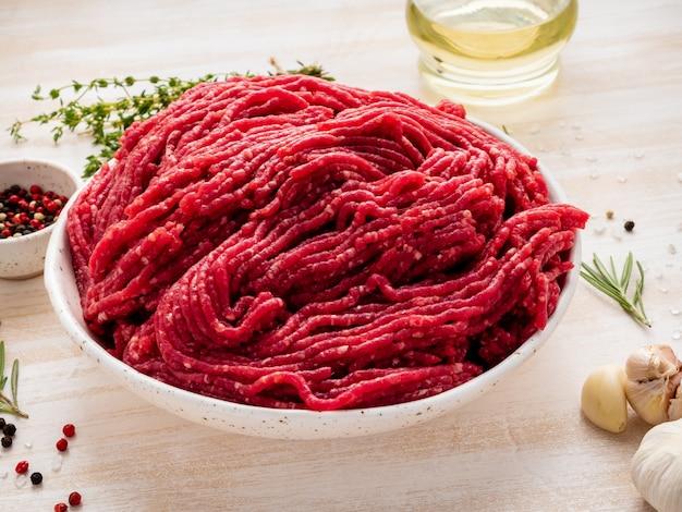 Carne picada, carne molida con ingredientes para cocinar en una mesa rústica de madera blanca