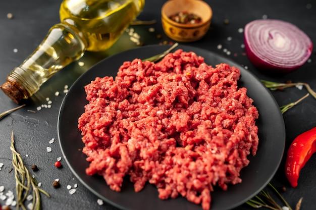 Carne picada cruda fresca con hierbas y especias en un plato negro sobre un fondo de piedra