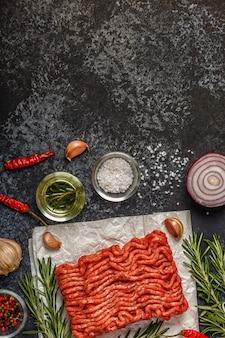 Carne picada cruda en papel con cebolla, hierbas y condimentos en bla
