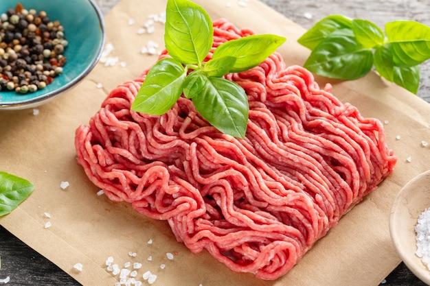 Carne picada con especias en papel sobre mesa. de cerca