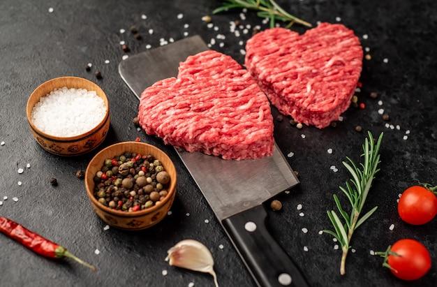 Carne picada en forma de corazón en un cuchillo sobre un fondo de piedra