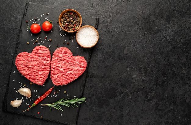 Carne picada en forma de corazón sobre un fondo de piedra con espacio para copiar el texto