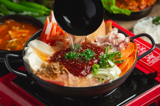 La carne picante y el cerdo hierven en una olla caliente.