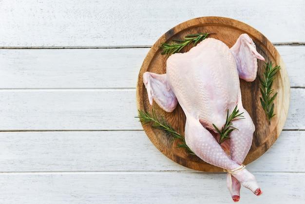 Carne de pollo al romero / pollo crudo fresco entero sobre tabla de madera sobre fondo de madera blanca