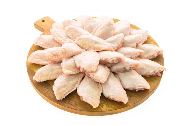 Carne de pollo cruda y ala en tabla de cortar de madera o placa