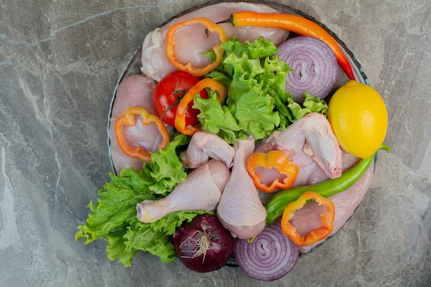 Carne de pollo cruda con verduras frescas sobre fondo de mármol. foto de alta calidad