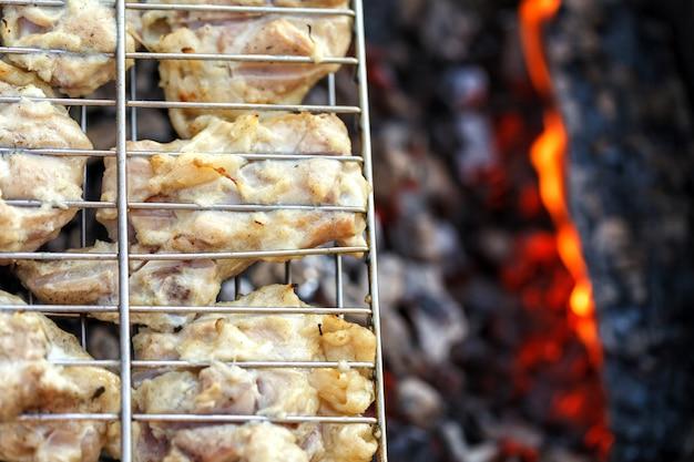 Carne de pollo frita en una parrilla de barbacoa.