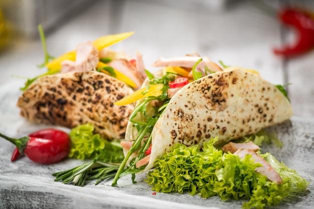 Carne de pollo frito con vegetales en pan de pita